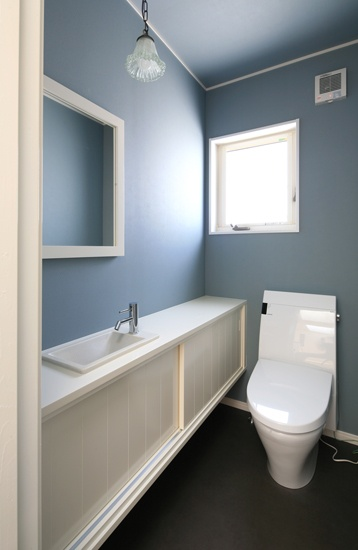 落ち着いた青みのあるグレーの壁紙。棚や便器の白さで、上品な雰囲気になっています。