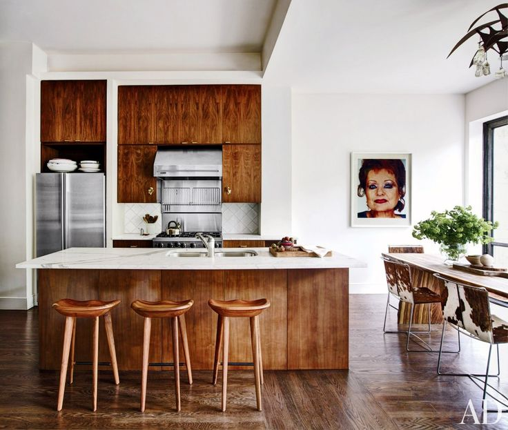 The addition of a slab of marble to the rich wooden island in this kitchen brightens its more rustic elements to make the space elegantly modern