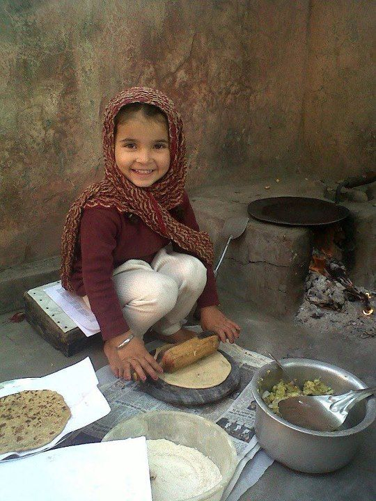 Rolling chapatis - never too early to start cooking! punjab India