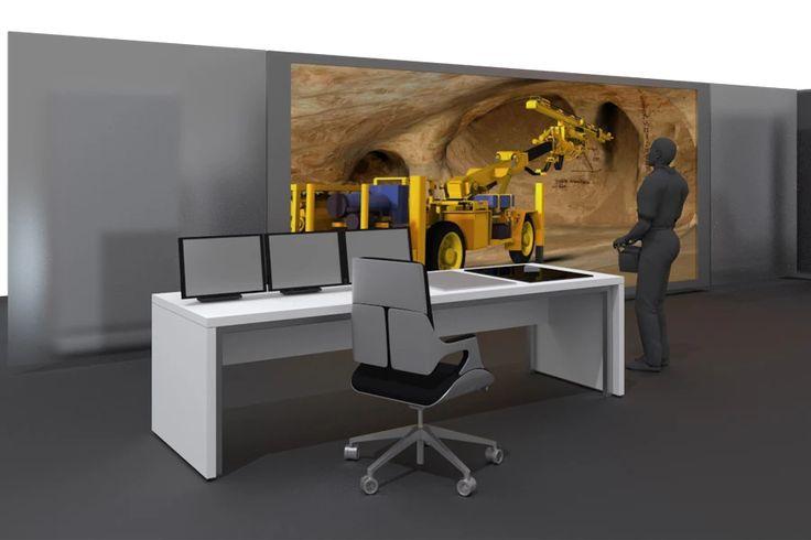 Schulungsumgebung für virtuelle Schulungen. Eine Projektionswand lässt Schulungsteilnehmende in die Simulation eines Bohrwagens unter Tage eintauchen. Der Simulator wird mit originalgetreuer Funk-Fernsteuerung bedient. Der digitale Zwilling lässt Auszubildende Bohrhauer alle Funktionen des Bohrwagens erleben.