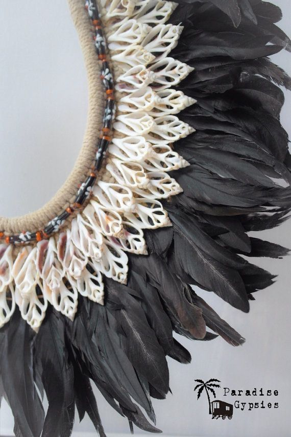 Necklace detail;  handmade necklace from Papua with two layers of white shells, two layers of black bead and straight black feathers.
