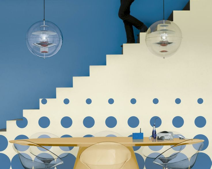 Plongez dans le grand bleu. Cette salle à manger a tout d'un aquarium avec ses murs bleu marine et ses bulles bleues sur le fond sablé du mur de l'escalier qui donnent du relief.