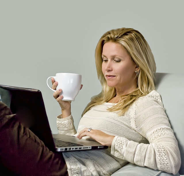 A young woman enjoys a cup of coffee while working from home. She ...