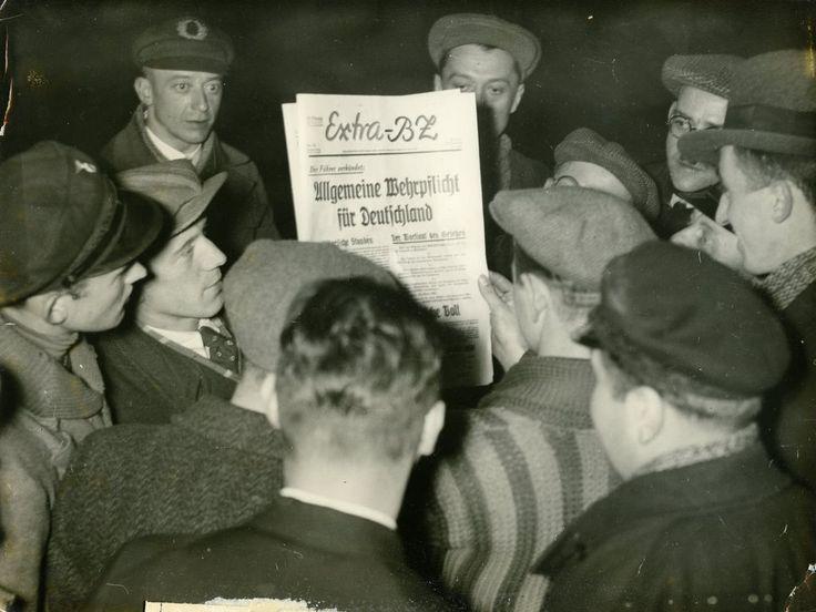 """Passanten lesen das Extra-Blatt der BZ mit der Schlagzeile """"Allgemeine Wehrpflicht für Deutschland"""", 1935. Newspaper proclaiming obligatory military service in Germany, 1935."""