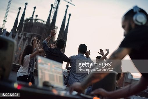 Stock Photo : Disc jockey playing on roof terrace with group of people dancing in background