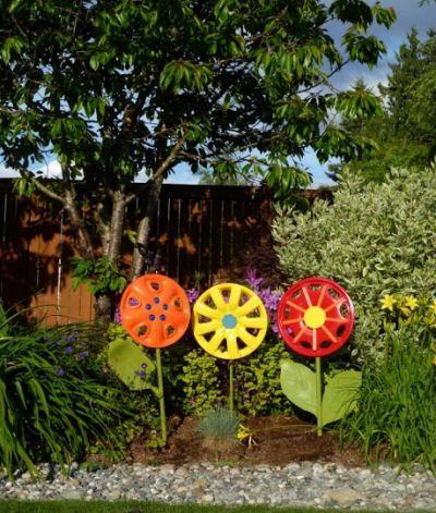 Hub cap flowers DIY yard decoration - I would probably have left them au naturel...