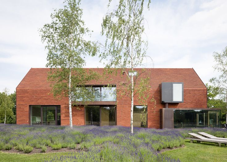 Terracotta tiles cover this house on Belgian farmland, which was designed to match the traditional agricultural architecture of the region