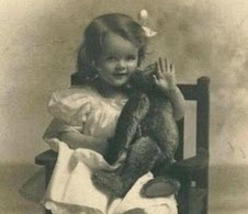 Antique photo of a little girl with her teddy bear.