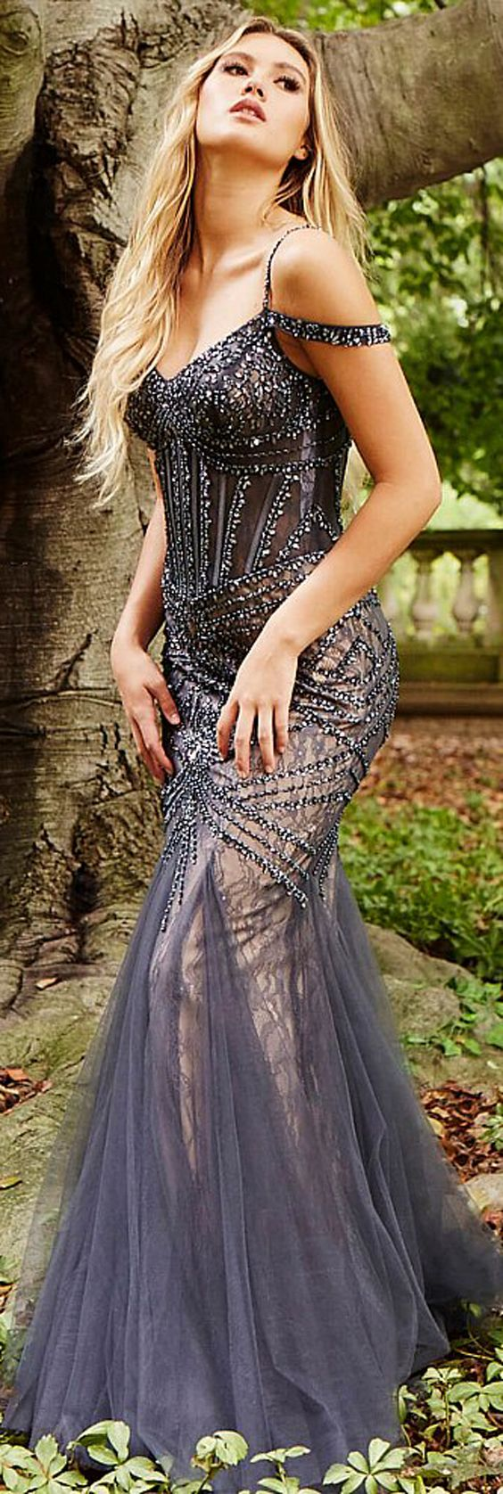 This #Jovani charcoal gray prom gown features a corset-boned sheer bodice, with cold-shoulder straps framing the sweetheart neckline and shallow V-back. Intricate tonal beadwork on tulle overlays this lace prom dress, ending in a godet skirt and sweep train. A nude lining creates a striking contrast to this trumpet formal dress.