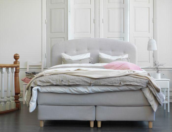 Zbliżenie na beżowe łóżko z pikowanym, wysokim zagłówkiem. W połączeniu z białą, szarą i beżową pościelą.