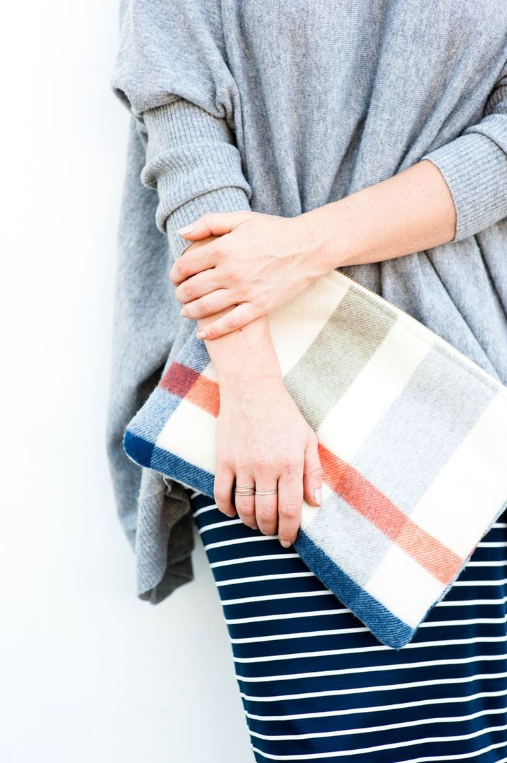Geometry in clothing: a striped skirt and a striped clutch with a grey oversized sweater