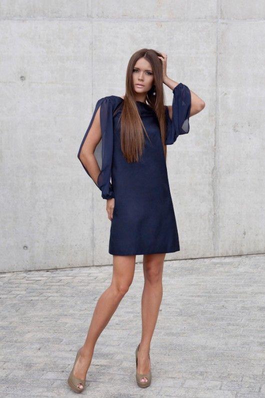 Sukienka trapezowa  uszyta z włoskiej  tkaniny z lekkim  połyskiem, kolor:  stonowany granat. Na  podszewce, rękawy  szyfonowe,  marszczone,  rozcięte. Z tyłu  ozdobne wiązanie na  szyfonową kokardkę.  Długość sukienki od  92 do 96cm w  zależności od  rozmiaru. Wymiary  ciała biust 86-...