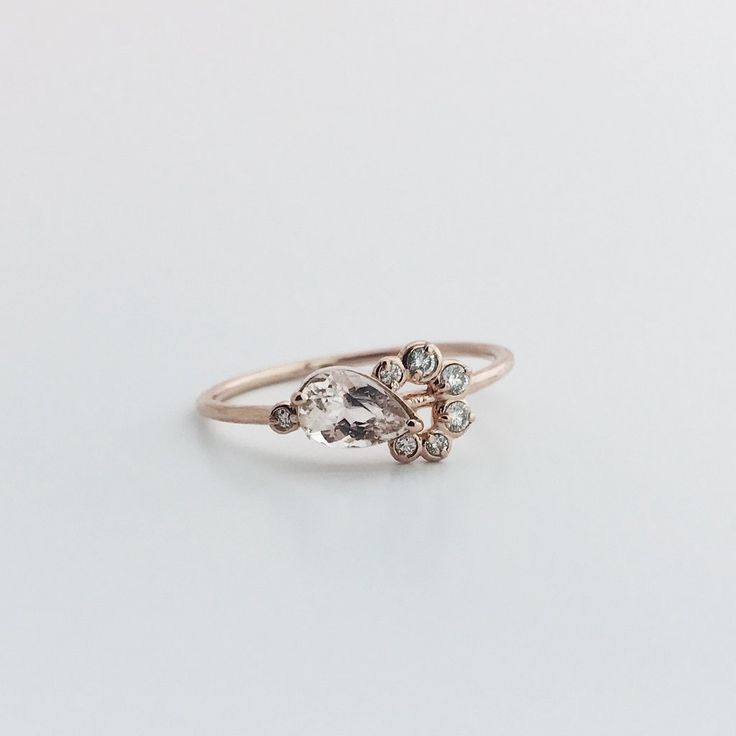 The cutest little pink morganite and white diamond stacking ring. A 14K rose gold band holds the 8 bezel set stones. This uniquely designed ring is a modern day heirloom and meant to be worn daily. -