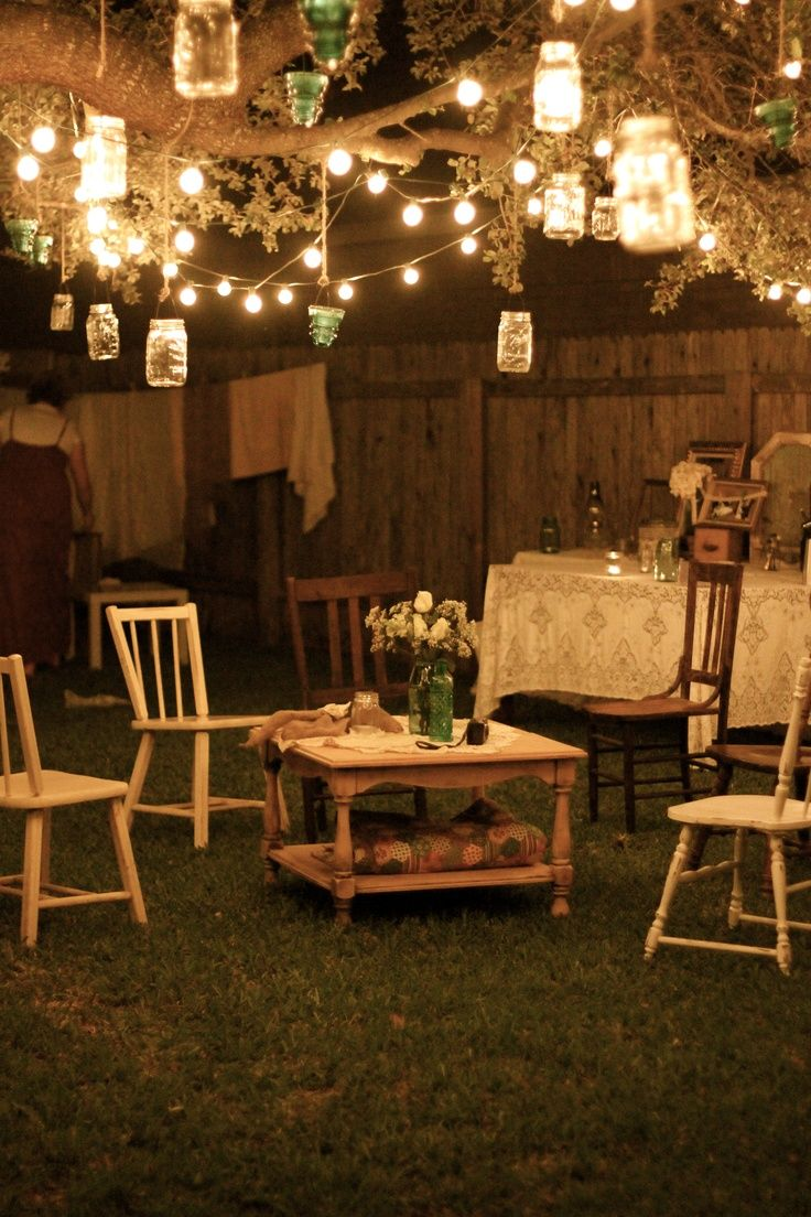 Garden party at night; lanterns hang from tree branches, and rustic furniture…
