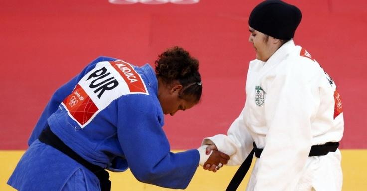 A judoca saudita Wojdan Shaherkani (dir.), de véu (hijab), foi a primeira mulher do seu país a competir em Jogos Olímpicos; ela é cumprimentada pela porto riquenha Melissa Mojica, que venceu a luta em apenas 1min22s
