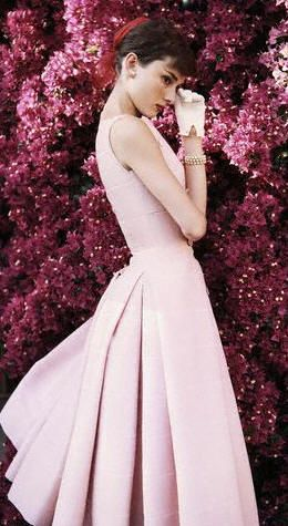 Audrey Hepburn in a pink dress, white gloves, and pearls.