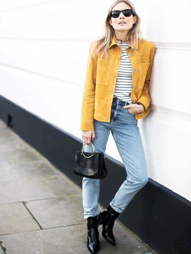 Lucy Williams in a tan suede cropped jacket, breton top, straight leg jeans, black patent ankle boots and carrying a circle handle bag.