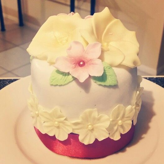 Small cake decorated with fondant flowers and ribon