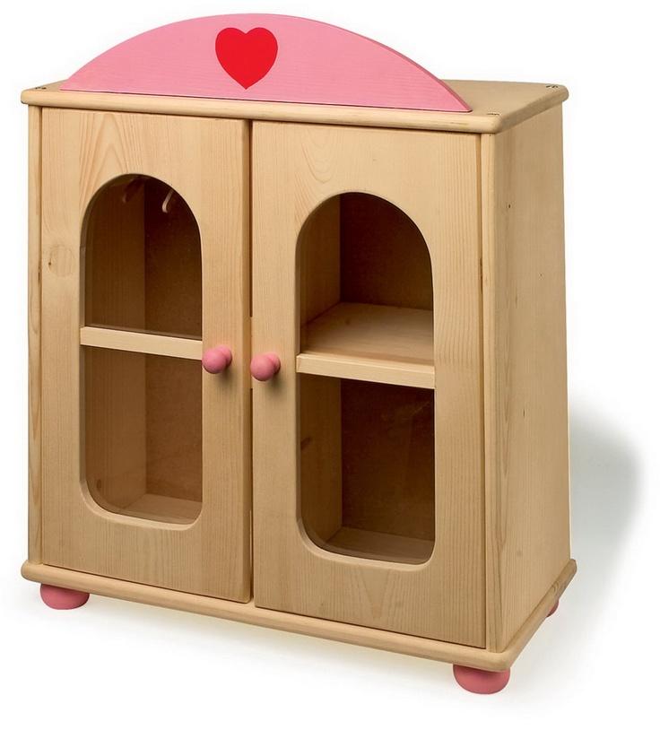 """Puppenschrank. Alles in einem Schrank untergebracht! Ein klassischer Holzschrank mit großem Innenraum und rosafarbenen Aufsatz mit Herzlogo im bewährten """"small foot design"""". Der massive Kleiderschrank für Puppenkleider bietet auf der linken Seite reichlich Platz zur Ablage von Kleidungsstücken und in der rechten Seite lassen sich auf die mitgelieferten Holzbügel Kleider, Blusen und Jacken aufhängen. So finden alle Puppenkleidungsstücke einen sicheren Aufbewahrungsort."""