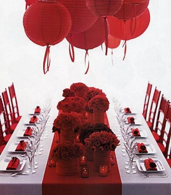 Go red! Roter Tischläufer, Servietten und Blumen in Dunkelrot und darüber rote Lampions