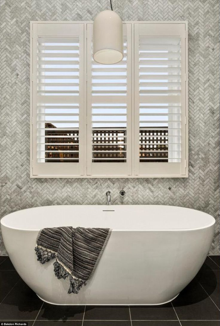 The main bathroom features a freestanding stone bathtub which serves the three large bedrooms