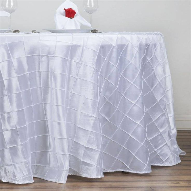 "White Pintuck Tablecloths 132"" Round - Pintuck is actually a fold of fabric that is stitched intricately to hold it in a place, very much like a pleat. These lovely pleats impart a decorative effect to the fabric by fashioning a visual line at a chosen point. They effortlessly bridge vintage and contemporary styles to create a majestic new classic look. If you do not want your celebration to blend in with other weddings, birthdays, and anniversaries, try our premium quality pintuck…"