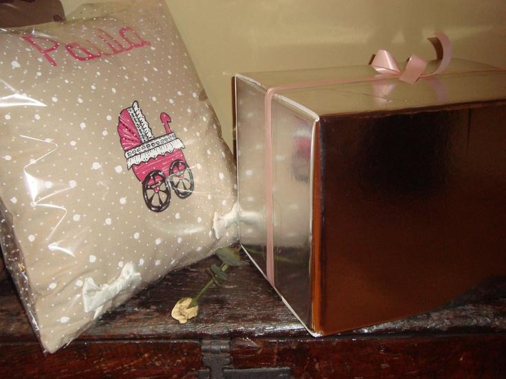 Envoltorio para la entrega: caja plateada con lazo rosa (niña) o lazo azúl (niño)  para vajilla y  papel transparente con lunares para cojín.