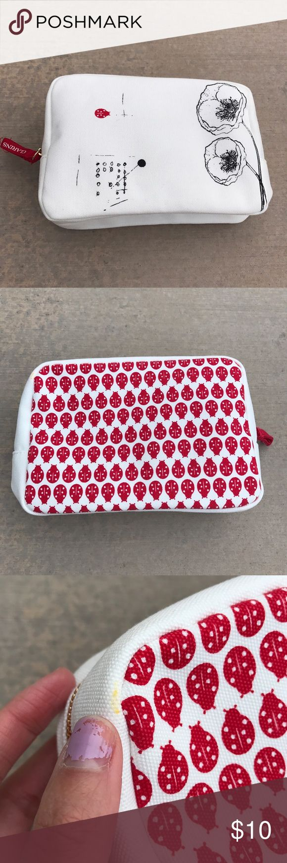 Clarins Ladybug Makeup Bag (NWOT) Canvas material makeup bag with ladybug graphics. Zipper closure. Never been used but has a light stain in one corner. Clarins Bags Cosmetic Bags & Cases