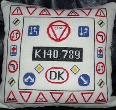 97069 Broderipakning - Bilpude med gamle vejskilte Design måler 27 x 27 cm Færdigmål af puden 35 x 35 cm Aida med 5,4 sting pr cm Pakningen indeholder mønster, garn, nål samt 2 stk. stof til både for- og bagside. Incl. alfabet og tal.  En hyggelig bilpude med 24 gamle vejskilte fra 60'erne. I midten er der en sort nummerplade med bilnummeret K 140.789 hvor man kan skrive sit eget bilnummer.