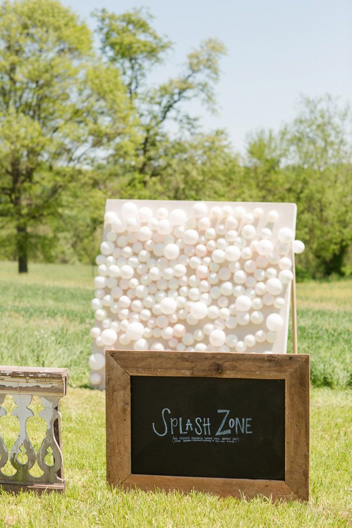 Guests throw darts at balloons with paint inside, the newlyweds keep the art