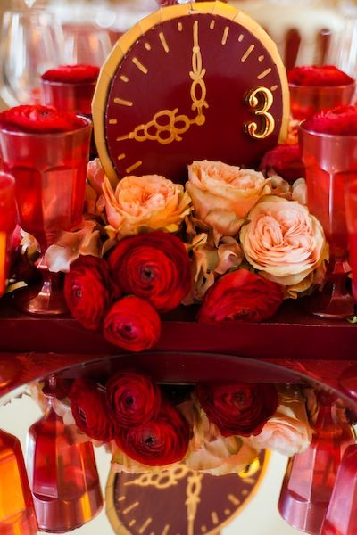 Red tone composition with golden lucky clock, mirror, red and peach tone roses.