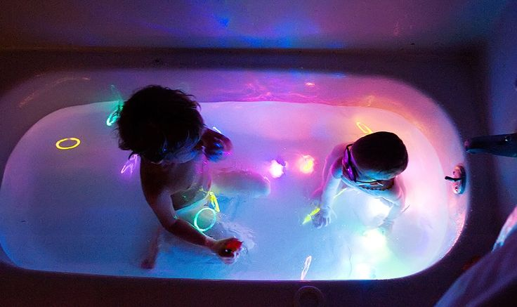 bebés en tina de baño con barritas fluorescentes de colores