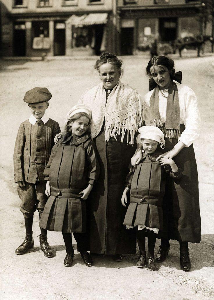 Mode. Kinderkleding. Een oudere en een jonge vrouw met drie kinderen die typisch Engelse kinderkleding uit 1915 dragen. De meisjes dragen grof geplooide jurkjes. Het jongetjes is gekleed in een plus-four, lange kousen, een jas met witte kraag en een pet.  Engeland, 1915.