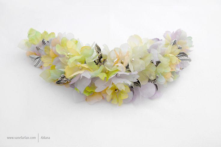 Tocado elaborado en flores de gasa y mini hojas en apliques color plata.
