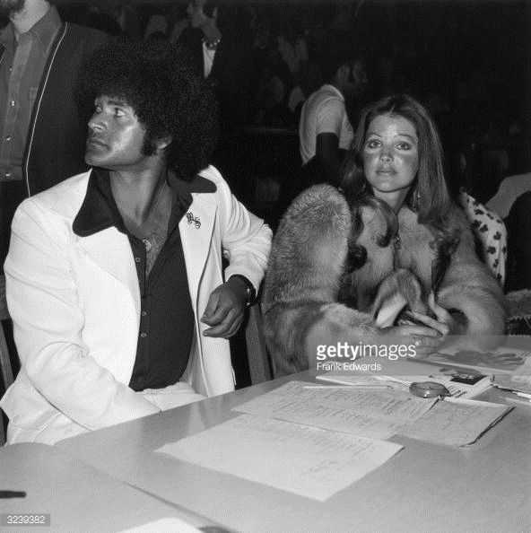 April 1975:  American actor Priscilla Presley sits with her boyfriend, karate instructor Mike Stone, at a kung fu tournament at the Beverly Hills High School, California. Description from gettyimages.com. I searched for this on bing.com/images