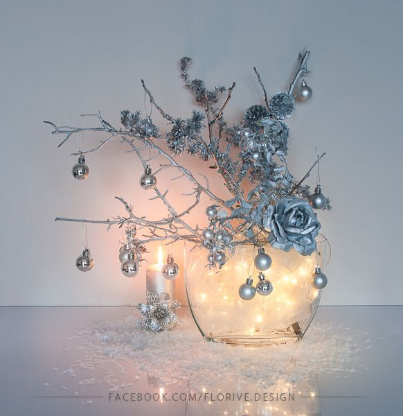 Silver Christmas decoration with fairy lights in the glass vase