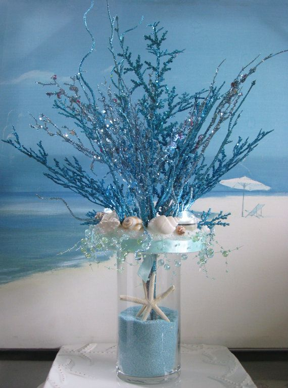 Blue Coral Seashell Sand Wedding Centerpiece  by CeShoreTreasures, $75.00/ 6 in strofoam ring glued to clear vase, blue satin ribbon and blue acrylic bubble garland[could use blue string pearls] around glued to Styrofoam ring, glitter paint coral and beach grass, blue sand and white starfish, pretty!