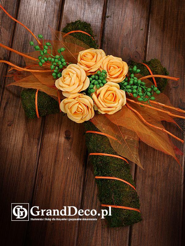 Krzyż z mchu z dekoracją z kwiatów sztucznych i suszu egzotycznego: farbowane gałązki canella, listki preparowane, ratan w paskach, farbowane patyczki. Wszystkie elementy do nabycia na www.GrandDeco.pl