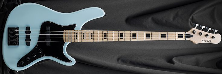 Kiesel Guitars JB4, light blue (LB), maple fingerboard (MF), block inlays (IB), black acrylic inlays (IAB), stainless steel frets (STF), headstock color matches body (PH), active/passive electronics (AC), black pickguard (BG), black hardware (BC), black logo (BL)