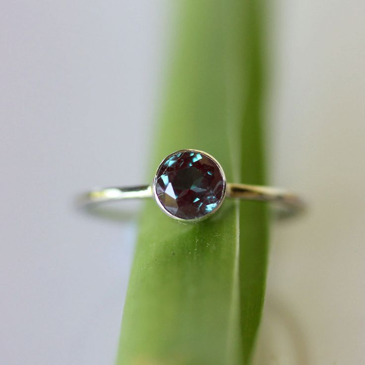 Alexandrite, a heart chakra stone that helps to let go of grief and bring joy. It changes color - reddish in artificial light, green/blue in daylight.