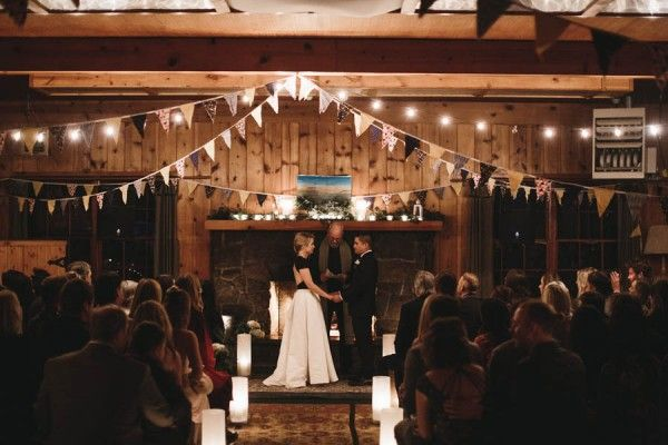 Cozy, log cabin wedding ceremony. | Image by Nicole Mason