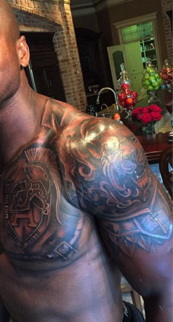 "As he rejoined the Minnesota Vikings, Adrian Peterson had some new artwork over his heart. The running back's new tattoo is designed to look like body armor, with a letter ""A"" and the inscription ""Shield of Faith"" over Peterson's heart. His left shoulder is tattooed with a lion, and a sword running down the middle of an open Bible."