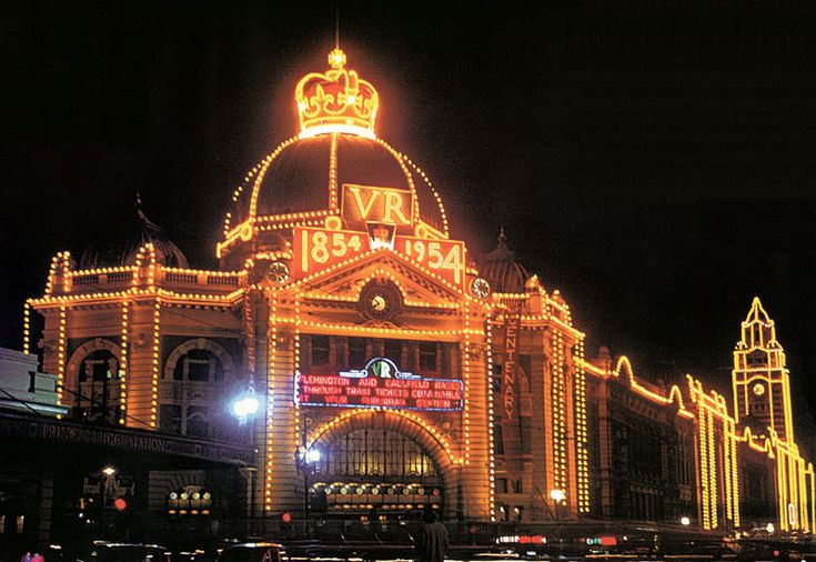 Flinder Street station at night festooned in lights in 1954 to celebrate the centenary of Victoria Railway and the Royal Visit