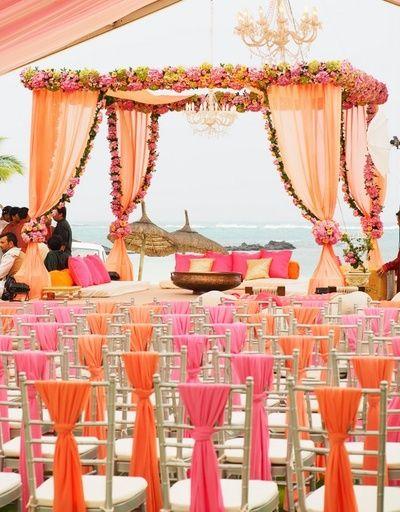 peach wedding mandap, mandap with chandelier, beach wedding decor, beachside mandap, floral curtains, peach and orange chair backs, candy pink, destination wedding decor