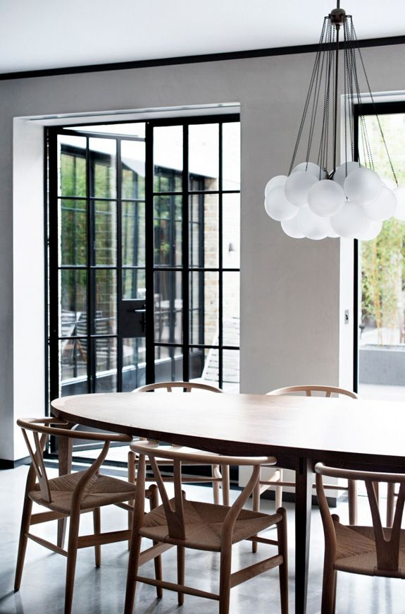 Dining: black steel-frame doors, grey polished concrete floor, Hans Wegner Wishbone chairs, oval wooden dining table