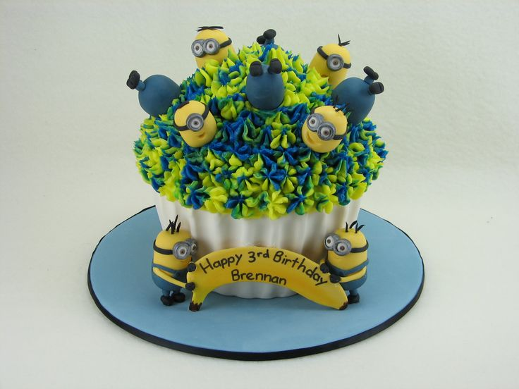 A giant mud cupcake with a fondant case and buttercream frosting on top. The minions are handmade from fondant.