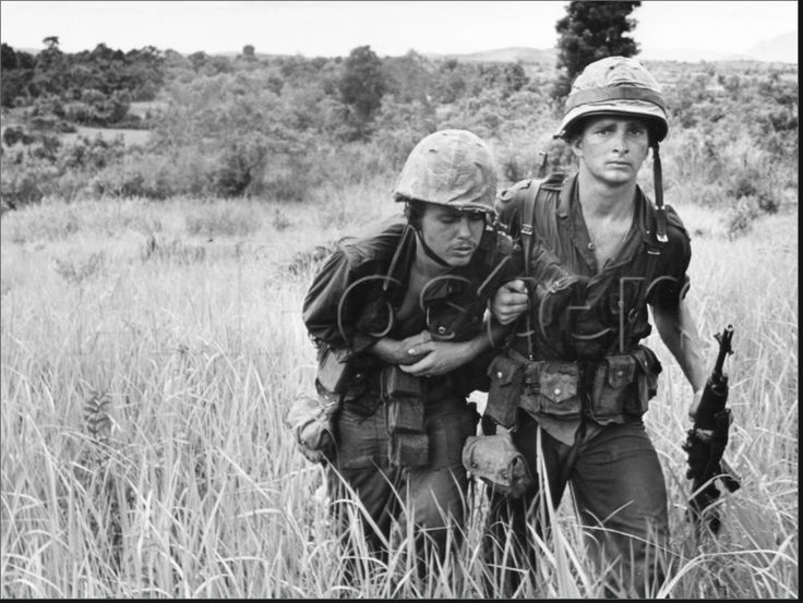 """A U.S. Marine helps his buddy find a medic as rockets continue to fall near the village of Duc An, 60 miles south of Da Nang, in early August 1965. Officials described U.S. casualties as """"light,"""" while reporting 17 Viet Cong dead."""