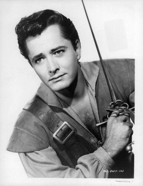 John Derek holding sword in publicity portrait for the film 'Prince Of Pirates' 1953