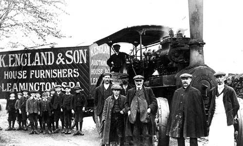 """Leamington Spa.  K. England & Son Steam engine hauling trailer with """"K. England & Son, House Furnishers, Leamington Spa"""" painted on side. Driver in cab, workmen and group of school boys posing by engine, Leamington Spa. 1900s"""