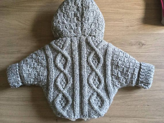 Manteau Lenzo taille 6 mois, tricoter en maille Irlandaise et doubler avec une laine douce. Elle porte bien son nom avec son toucher peau de pêche. Ce fil fantaisie à la texture pelucheuse va plaire à bébé. Tricotés dans une laine layette de qualité, adaptée pour votre bébé qui garde